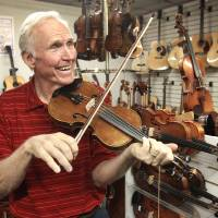 Photo - Byron Berline is shown at his Double Stop Fiddle Shop in Guthrie. He had a group in the 1970s called Sundance. One of the members was Vince Gill, who in October will headline the Oklahoma International Bluegrass Festival in Guthrie. Photo by David McDaniel, The Oklahoman