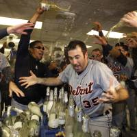 Photo -   Detroit Tigers' Justin Verlander (35) is drenched with sparkling wine by teammates at the end of Game 5 of during the American League division baseball series in Oakland, Calif., Thursday, Oct. 11, 2012. (AP Photo/Ben Margot)