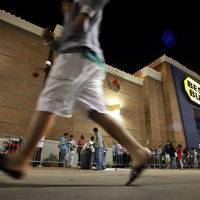 Photo -   Shoppers stand in line outside a Best Buy department store before the store's opening at midnight for a Black Friday sale, Thursday, Nov. 22, 2012, in Arlington, Texas. Despite a surge of resistance as the sales drew near, with scolding editorials and protests by retail employees and reminders of frantic tramplings past, Black Friday's grip on America may have been proven stronger than ever. (AP Photo/Tony Gutierrez)