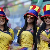 Photo - Fans of the Colombia team smile posing for the photographer before the group C World Cup soccer match between Japan and Colombia at the Arena Pantanal in Cuiaba, Brazil, Tuesday, June 24, 2014. (AP Photo/Dolores Ochoa)