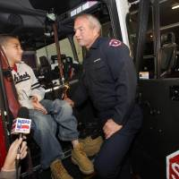 Photo -   Koregan Quintanilla, 10, of Watauga, Texas, left, talks to firefighter Wesley Keck as they prepare to take a short trip around the neighborhood on a fire truck Thursday, Nov. 15, 2012, in Arlington, Texas. Quintanilla, who was abandoned at a fire station as an infant, celebrated his recent birthday by meeting Keck, the firefighter who saved him, riding on a fire truck and touring the station. (AP Photo/Tony Gutierrez)