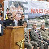 Photo - Bolivia's President Evo Morales, left, announces that he is nationalizing the Spanish-owned venture, SABSA, that runs the country's three main airports, at the Jorge Wistermann Airport in Cochabamba, Bolivia, Monday, Feb. 18, 2013. The affected company, SABSA, runs the airports in the cities of La Paz, Santa Cruz and Cochabamba. Morales' move Monday is the latest in a series of nationalizations he has ordered of mostly Spanish investments in what he considers public utilities. (AP Photo)