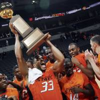 Photo - OSU's Marshall Moses (33) raises the trophy after the college basketball game between Oklahoma State University (OSU) and La Salle University in the All College Basketball Classic at the Ford Center on Monday, Dec. 21, 2009, in Oklahoma City, Okla. OSU won, 77-62.  Photo by Nate Billings, The Oklahoman ORG XMIT: KOD