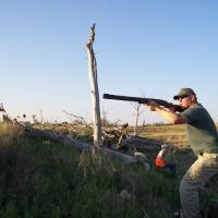 Photo - Chris Shelton takes aim around a farm pond during a dove hunt. Oklahoma's dove season is currently open and runs through Oct. 31.  Photo provided