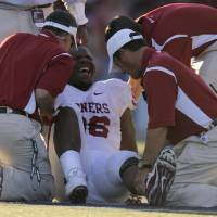 Photo - Oklahoma's DeMarcus Granger (96) reacts in pain as trainers tend to an injury in the first half during the college football game between the University of Oklahoma (OU) and University of Washington at Husky Stadium in Seattle, Wash., Saturday, September 13, 2008. BY NATE BILLINGS, THE OKLAHOMAN ORG XMIT: KOD