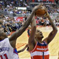 Photo - Washington Wizards forward Trevor Ariza, center, puts up a shot as Los Angeles Clippers guard Jamal Crawford, left, defends and forward Grant Hill watches during the first half of their NBA basketball game, Saturday, Jan. 19, 2013, in Los Angeles.  (AP Photo/Mark J. Terrill)