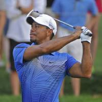Photo - Tiger Woods hits his fairway shot on the second hole, during the third round of the Bridgestone Invitational golf tournament, Saturday Aug. 2, 2014, in Akron, Ohio. (AP Photo/Phil Long)