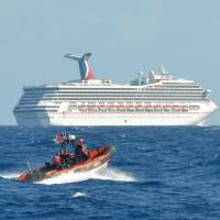 Photo - In this image released by the U.S. Coast Guard on Feb. 11, 2013, a small boat belonging to the Coast Guard Cutter Vigorous patrols near the cruise ship Carnival Triumph in the Gulf of Mexico, Feb. 11, 2013. The Carnival Triumph has been floating aimlessly about 150 miles off the Yucatan Peninsula since a fire erupted in the aft engine room early Sunday, knocking out the ship's propulsion system. No one was injured and the fire was extinguished. (AP Photo/U.S. Coast Guard- Lt. Cmdr. Paul McConnell)