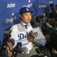 Photo - New Los Angeles Dodgers pitcher Ryu Hyun-jin, of South Korea, takes questions from reporters following a baseball news conference announcing his $36 million, six-year contract, Monday, Dec. 10, 2012, in Los Angeles. Ryu becomes the first player to go directly from the Korea Baseball Organization to the United States big leagues. (AP Photo/Damian Dovarganes)