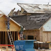 Photo - Construction workers build a new home on a lot next to a home that still looks like it did  the day the tornado passed through this neighborhood at  SW 144 and Briarcliff.    Retracing path of the May 20, 2013 tornado, six months later, on Nov. 19, 2013, the 6-month anniversary of this deadly and violent twister.   Photo by Jim Beckel, The Oklahoman