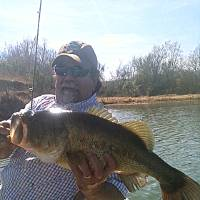 Photo - Scotty Taylor of Norman holds an 8-pound largemouth bass caught from a McClain County farm pond. Photo by Spencer Taylor