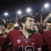 Photo - Stanford quarterback Andrew Luck, center, smiles with teammates after Stanford defeated Notre Dame 28-14 in an NCAA college football game in Stanford, Calif., Saturday, Nov. 26, 2011. (AP Photo/Paul Sakuma) ORG XMIT: CAPS121