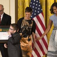 Photo - The Children's Museum of Indianapolis President and CEO Jeffrey Patchen, left, holds the museum's 2014 National Medal for Museum and Library Service as Spencer Hahn, 8, who had a stroke in-utero, whistles by his mother Erica Hahn and first lady Michelle Obama during a ceremony in the East Room of the White House, Thursday, May 8, 2014, in Washington. The National Medal is the nation's highest honor given to museums and libraries for service to the community. (AP Photo/Jacquelyn Martin)