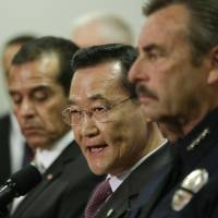 Photo - Irvine, Calif., Mayor Steven Choi, center, talks about the $1,000,000 reward for accused killer and fired Los Angeles police officer, Christopher Dorner as Los Angeles Mayor, Antonio Villaraigosa, left, and Los Angeles Police Chief Charlie Beck look on during a new conference at the Los Angeles police department in Los Angeles, Sunday, Feb. 10, 2013.  (AP Photo/Chris Carlson)