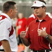 Photo - Cincinnati Head coach Butch Jones (left) talks with head coach Bob Stoops before the college football game between the University of Oklahoma Sooners (OU) and the University of Cincinnati Bearcats (UC) at Paul Brown Stadium on Saturday, Sept. 25, 2010, in Cincinnati, Ohio.   Photo by Steve Sisney, The Oklahoman