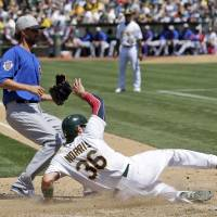 Photo - Oakland Athletics' Derek Norris, right, scores on a passed ball by Chicago Cubs catcher Welington Castillo next to Chicago Cubs reliever Matt Guerrier, left, during the seventh inning of an MLB baseball game on Thursday, July 4, 2013, in Oakland, Calif. (AP Photo/Marcio Jose Sanchez)