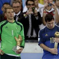 Photo - Germany's goalkeeper Manuel Neuer, recipient of the Golden Glove trophy, stands next to Argentina's Lionel Messi after he receive the Golden Ball trophy following Germany's 1-0 victory over Argentina after the World Cup final soccer match between Germany and Argentina at the Maracana Stadium in Rio de Janeiro, Brazil, Sunday, July 13, 2014. (AP Photo/Natacha Pisarenko)
