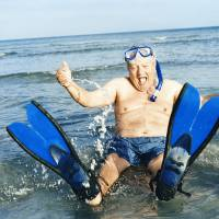 Photo - Senior Man Sitting in Shallow Sea Wearing Flippers, Scuba Mask and a Snorkel