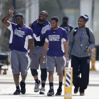 Photo - Unidentified Northwestern football players walk between their locker room and McGaw Hall, where voting is taking place on the student athlete union question Friday, April 25, 2014, in Evanston, Ill. Northwestern football players cast secret ballots Friday in an on-campus hall adjacent to their home stadium on whether to form the nation's first union for college athletes. (AP Photo/Charles Rex Arbogast)