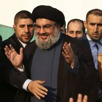 Photo -   In this Monday, Sept. 17, 2012 photo, Hezbollah leader Sheik Hassan Nasrallah, center, waves to his supporters, in the southern suburb of Beirut, Lebanon. The leader of the Lebanese militant Hezbollah group has claimed responsibility for launching the drone aircraft that entered Israeli airspace earlier this week. The rare admission Thursday by Hassan Nasrallah raises regional tensions at a sensitive time when the group's backers, Syria and Iran, are under pressure. (AP Photo/Hussein Malla)
