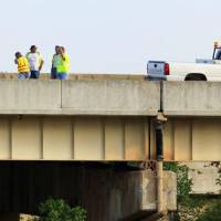 Photo - Oklahoma Department of Transportation workers and vehicle are shown in the far left eastbound lane of Interstate 44 on the Belle Isle bridge where it crosses over the Northwest Expressway in Oklahoma City on Monday. Two eastbound lanes were closed when an expansion joint, shown just right of the center in the photo, failed, causing damage to vehicles traveling on the highway. Photo by Paul B. Southerland, The Oklahoman  PAUL B. SOUTHERLAND