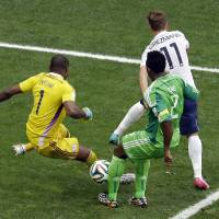 Photo - Nigeria's Joseph Yobo, front, scores an own goal to give France a 2-0 lead during the World Cup round of 16 soccer match between France and Nigeria at the Estadio Nacional in Brasilia, Brazil, Monday, June 30, 2014. (AP Photo/Hassan Ammar)