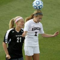 Photo - Edmond Memorial's Hannah Molone heads the ball next to Norman North's Mackenzie Marquadt during the Class 6A girls soccer championship between Edmond Memorial and Norman North in Norman, Okla., Friday, May 16, 2014. Photo by Bryan Terry, The Oklahoman
