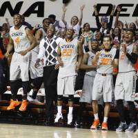 Photo - The Oklahoma State bench celebrates after forward Mason Cox makes a slam dunk late in an NCAA college basketball game against Kansas State held in Stillwater, Okla., Monday, March 3, 2014. Oklahoma State won 77-61. (AP Photo/The Oklahoman, KT King)