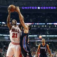 Photo - Chicago Bulls forward Jimmy Butler (21) shoots over Charlotte Bobcats guard Jeffery Taylor during the first half of an NBA basketball game, Monday, Jan. 28, 2013, in Chicago. (AP Photo/Charles Rex Arbogast)