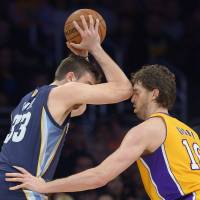 Photo - Memphis Grizzlies center Marc Gasol, left, of Spain, appears to make contact with the face of his brother Los Angeles Lakers forward Pau Gasol, during the first half of their NBA basketball game, Friday, April 5, 2013, in Los Angeles. Marc Gasol received a foul on the play and then a technical foul for adjuring the call.  (AP Photo/Mark J. Terrill)