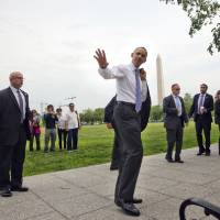 Photo - President Barack Obama waves to tourists during his surprise walk along the Ellipse in Washington, Wednesday, May 21, 2014. Obama walked to the Department of the Interior to sign a proclamation regarding the Organ Mountains-Desert Peaks National Monument. (AP Photo/Pablo Martinez Monsivais)