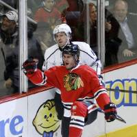 Photo - Chicago Blackhawks left wing Brandon Saad (20) celebrates his goal as Los Angeles Kings center Mike Richards skates behind during the first period of an NHL hockey game Monday, Dec. 30, 2013, in Chicago. (AP Photo/Charles Rex Arbogast)
