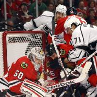 Photo - Several Chicago Blackhawks and Los Angeles Kings players crash into the goal crease near goalie Corey Crawford during the first period of an NHL hockey game, Monday, March 25, 2013, in Chicago. (AP Photo/Charles Rex Arbogast)
