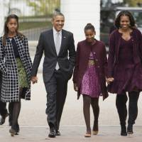 Photo - FILE - In this Oct. 27, 2013, file photo, President Barack Obama, second from left, with first lady Michelle Obama, right, and their daughters Malia, left, and Sasha, walk from the White House in Washington to attend a church service. Obama is encouraging more employers to adopt family-friendly policies by hosting a daylong summit, even though the U.S. government doesn't always set the best example. The United States is the only industrialized nation that doesn't mandate paid leave for mothers of newborns, although Obama says he'd like to see that change. (AP Photo/Manuel Balce Ceneta, File)