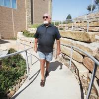 Photo - Tom Howard, a stroke patient, walks outside at Integris Health Edmond, where he was the hospital's first emergency room patient when it opened in 2011.