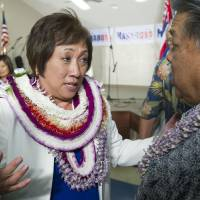 Photo - U.S. Rep. Colleen Hanabusa, Democrat, from Hawaii's 1st district, talks to former Hawaii Governor Ben Cayetano, right, at her campaign headquarters Saturday, Aug. 9, 2014, in Honolulu. Hanabusa is locked in a tight race with incumbent Sen. Brian Schatz in the state's Primary Election. (AP Photo/Eugene Tanner)