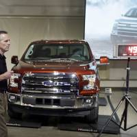 Photo - Ford Truck Group Marketing Manager Doug Scott stands next to the automaker's new aluminum-sided 2015 F-150 truck at the company's Development Center in Dearborn, Mich., Tuesday, July 22, 2014. The truck, which goes on sale this fall, is 732 pounds lighter than the outgoing model. Ford's base truck with a 3.5-liter V6 engine, will get 283 horsepower, similar to a Chevrolet Silverado but lower than a Ram. But Ford says it will have more towing capacity than both rivals, at 7,600 pounds. (AP Photo)