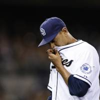 Photo - San Diego Padres starting pitcher Tyson Ross wipes his face with his jersey as he walks off the field at the end of the fourth inning while playing the Washington Nationals in a baseball game Friday, June 6, 2014, in San Diego. (AP Photo/Gregory Bull)