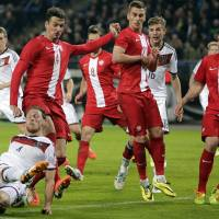 Photo - Germany's Benedikt Hoewedes, bottom, and Poland's Lukasz Szukala challenge for the ball during a friendly soccer match between Germany and Poland in Hamburg, Germany, Tuesday, May 13, 2014.  (AP Photo/Matthias Schrader)