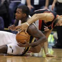 Photo - Utah Jazz forward Paul Millsap, left, works to keep control of a loose ball as Portland Trail Blazers forward Nicolas Batum, right, of France, tries to take it in the first half during an NBA basketball game on Friday, Feb. 1, 2013, in Salt Lake City. (AP Photo/Steve C. Wilson)