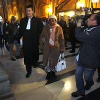 Photo -   Agathe Habyarimana, center, the widow of former President of Rwanda Juvenal Habyarimana, arrives with her lawyer Philippe Meillac, left, at a Paris court house, Tuesday, Jan. 10, 2012. A French investigator is releasing the results of his investigation Tuesday into the downing of the plane of President Juvenal Habyarimana, which helped spark Rwanda's 1994 genocide. (AP Photo/Remy de la Mauviniere)
