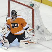 Photo - Philadelphia Flyers' Ilya Bryzgalov (30), of Russia, makes a glove save in the third period of an NHL hockey game against the Boston Bruins, Saturday, March 30, 2013, in Philadelphia. The Flyers won 3-1. (AP Photo/Michael Perez)