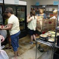 Photo -  Volunteers and clients load food items into baskets at Project 66. Photo by Paul Hellstern, The Oklahoman   PAUL HELLSTERN -