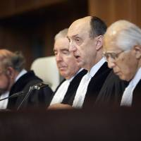 Photo - Judge Peter Tomka, center, president of the International Court of Justice, delivers its verdict in The Hague, Netherlands, Monday March 31, 2014. The International Court of Justice is ruling Monday on Australia's challenge against Japan for whaling in Antarctic waters. (AP Photo/Phil Nijhuis)