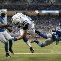 Photo - Indianapolis Colts tight end Coby Fleener (80), defended by Detroit Lions free safety Louis Delmas (26) and linebacker DeAndre Levy (54), falls into the end zone for a touchdown during the second quarter of an NFL football game at Ford Field in Detroit, Sunday, Dec. 2, 2012. (AP Photo/Paul Sancya)
