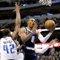 Photo - Oklahoma City Thunder guard Russell Westbrook (0) drives around Dallas Mavericks forward Elton Brand (42) during the first half of an NBA basketball game, Friday, Jan. 18, 2013, in Dallas. (AP Photo/Matt Strasen) ORG XMIT: TXMS202