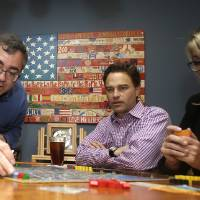 Photo - In this photo taken Thursday, Jan. 9, 2014, Spirit Airlines CEO Ben Baldanza center, and DeAnne Gabel, director Investor relations, right, play a game of Power Grid at Baldanza's home, in Fort Lauderdale, Fla. (AP Photo/Alan Diaz)