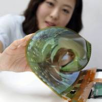 Photo - In this July 9, 2014 photo released by LG Display Co., an employee at the company demonstrates an 18-inch flexible display, in Seoul, South Korea. The South Korean display panel maker said Friday, July 11, 2014 it has developed the 18-inch flexible display that can be rolled into the shape of a thin cylinder, a step closer to making a large-size display for flexible TVs. (AP Photo/LG Display Co.)
