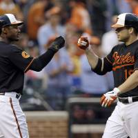 Photo - Baltimore Orioles' Adam Jones, left, greets teammate Chris Davis at home plate after Davis batted Jones in on a home run in the second inning of a baseball game against the Toronto Blue Jays, Friday, July 12, 2013, in Baltimore. (AP Photo/Patrick Semansky) ORG XMIT: MDPS104