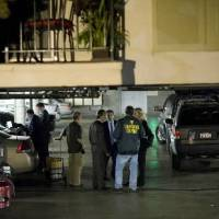 Photo - FBI agents stand in the ground floor parking garage of the apartment building in Santa Monica, Calif., where fugitive crime boss James